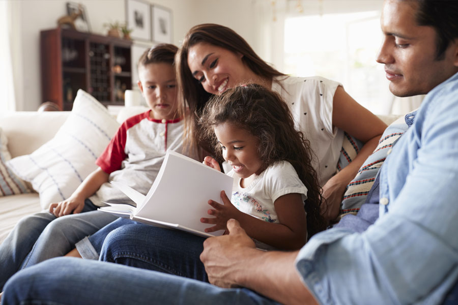 Blog - Family Sitting on the Couch Reading a Book Together