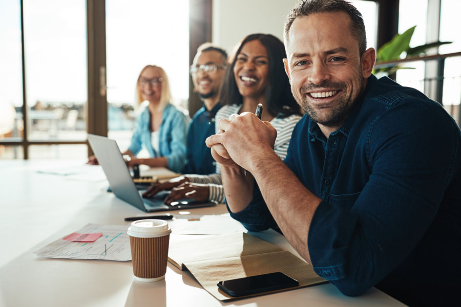 Business Insurance - Group of Men and Women at a Conference Table Smiling